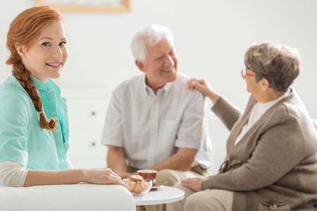 Jonge mooie verpleegster in een pension met haar patiënten Stockfoto
