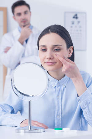 Young woman in front of mirror,  trying on contact lens