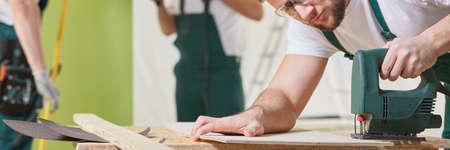 Man carpenter at work using professional jigsaw, panorama Stock Photo