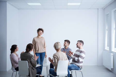 Happy woman talking in front of group during psychotherapy Imagens