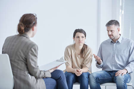 Angry married couple talking with psychologist during therapy