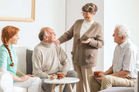 Group of older friends and young nurse spending time at retirement club