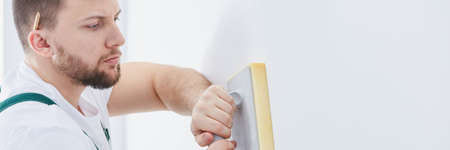Professional man with sponge float plastering white wall