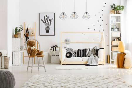 Weißes Kinderzimmer mit Teppich, Sitzpuff, Stuhl, Bett und Bücherregal Standard-Bild - 74570358