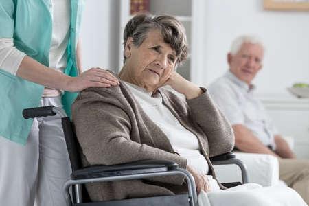 Preocupado mujer mayor en una silla de ruedas en un asilo de ancianos Foto de archivo