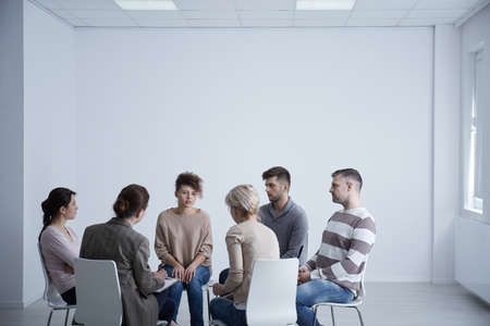 Therapist and his patients sitting in circle during meeting Stock Photo