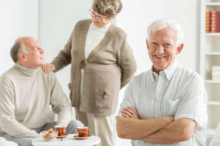 common room: Happy older man in a white cozy nursing home
