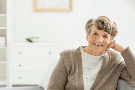 Happy older elegant woman sitting in a white nursing home Stock Photo