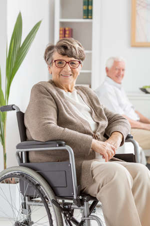 Elderly disabled woman on a wheelchair in nursing home