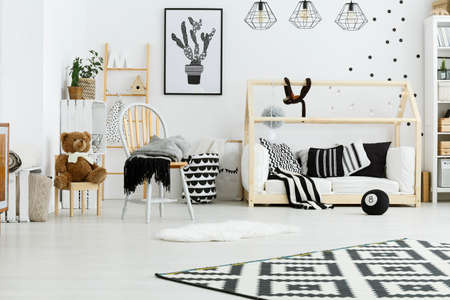 poster bed: Baby room with wooden house bed, lamps, chair and rug