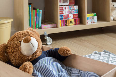 Childrens room interior with a teddy bear in bed and sliding shelf with toys