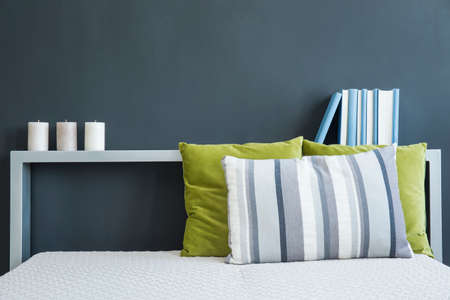 kingsize: Bed with green and blue pillows and shelf with candles and books against black wall