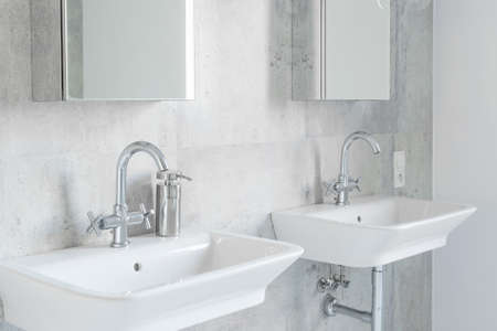 Minimalist modernist bathroom interior with two sinks and mirrors