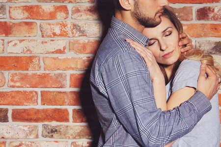Knappe man knuffelen zijn vriendin tegen bakstenen muur