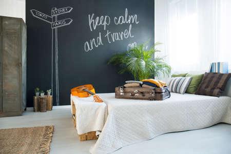 kingsize: Bed in modern travel-themed bedroom with blackboard wall