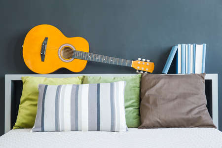 kingsize: King-size bed with colorful pillows, guitar and books