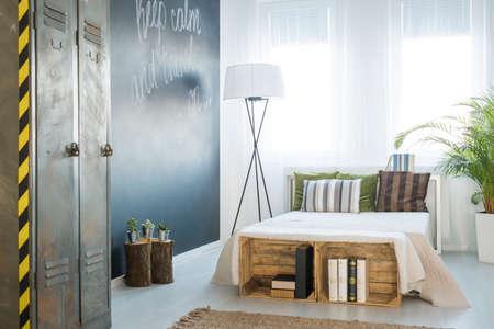 Cozy modern bedroom with big windows and chalkboard wall