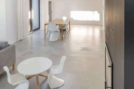 Spacious,minimalistic dining room in white tonation with modernist tables and chairs Stock Photo