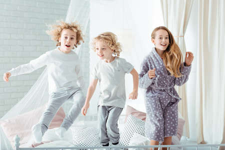 Small brothers and sister jumping on bed Фото со стока