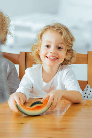 Happy small boy eating healthy watermelon, sitting beside table