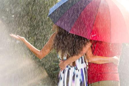 Uomo e donna sotto l'ombrello arcobaleno sotto la pioggia estiva