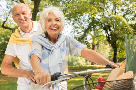 シニア カップル公園でタンデム自転車に乗って