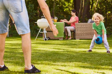 小さな息子の庭で父とラグビー ボールをプレー