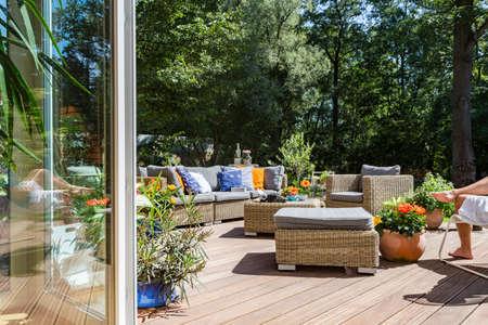 Nieuw stijl villa terras met rotan meubel set en decoratieve bloemen