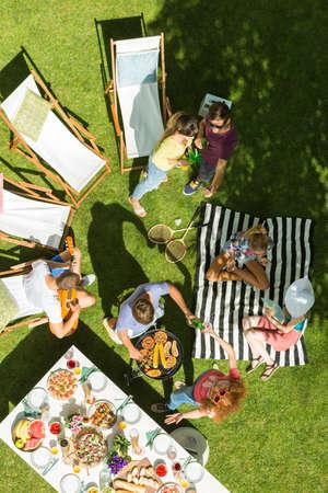 Bovenaanzicht van een groep vrienden met een picknick in de tuin