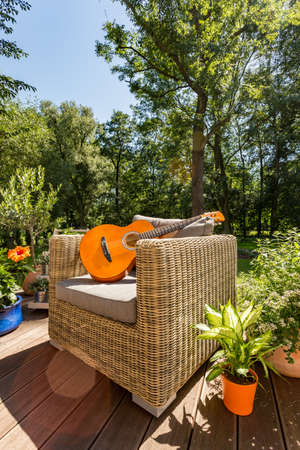 Guitar lying on a rattan garden sofa during sunny summer day