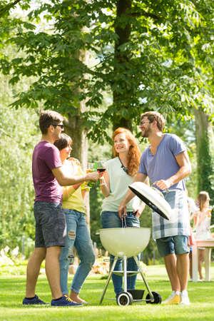 Group of young people enjoying grill party in park