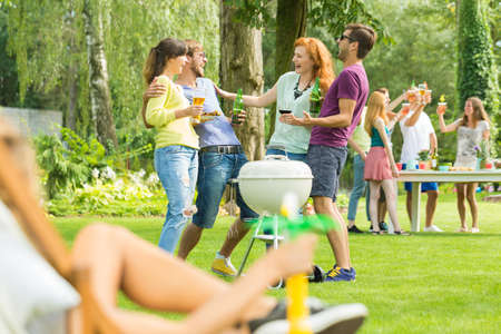 Young people grilling and drinking in garden