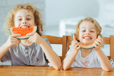 Adorable, happy siblings eating healthy watermelon, sitting beside table