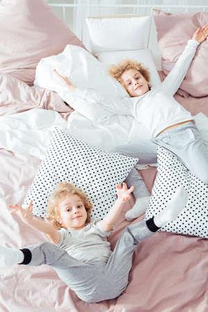 Small brothers lying in bed, having fun Фото со стока