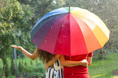 Couple under rainbow umbrella walking in the summer rain