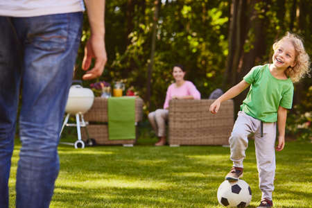 Child playing soccer ball with father in garden