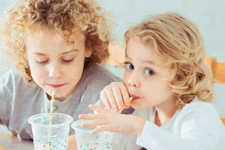 Cute, small siblings drinking healthy milk, sitting beside table Stock Photo