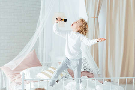 Small boy with microphone singing, standing on bed
