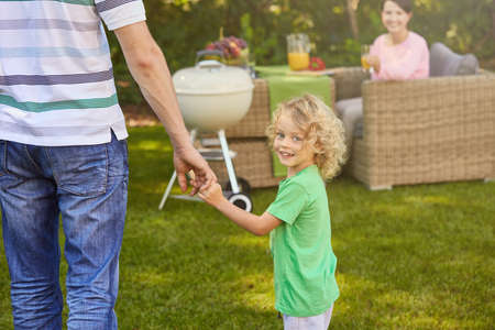 rattan: Small boy holding fathers hand while walking in garden Stock Photo