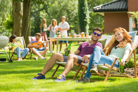 Young couple sitting on deckchairs during garden party