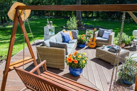 Ruime villapatio met tuinschommel, rotan meubelset, grill en gitaar in de zomer Stockfoto
