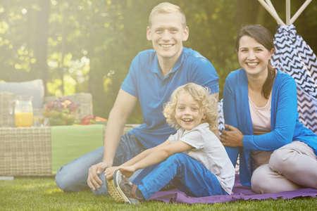matrimonio feliz: matrimonio feliz con el niño sentado sobre una manta en el jardín