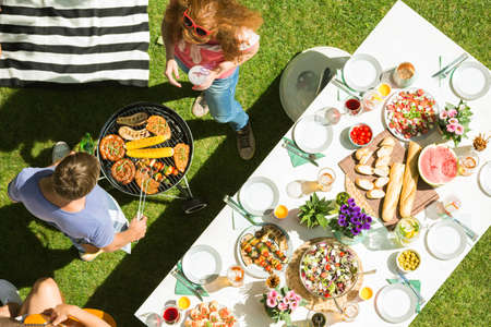 Man and woman grilling food for party garden, top view