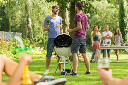 Two men standing beside barbecue grill in garden