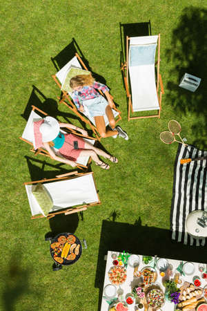 Top view of women lying on deckchairs in garden Stock Photo