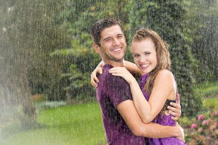 pareja abrazada: Feliz el hombre y la mujer de pie en la lluvia de verano Foto de archivo