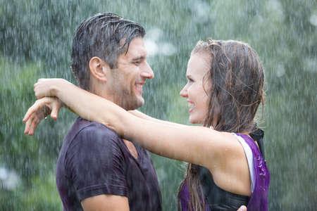 夏の雨に美しい幸せなロマンチックなカップルの立っています。