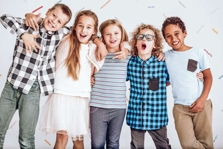 Group of happy kids standing in a row and smiling Stock Photo