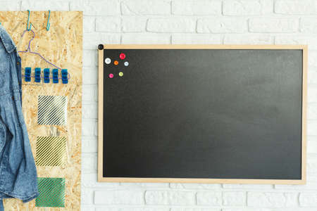 Blackboard with magnets and osb board in room with brick wall