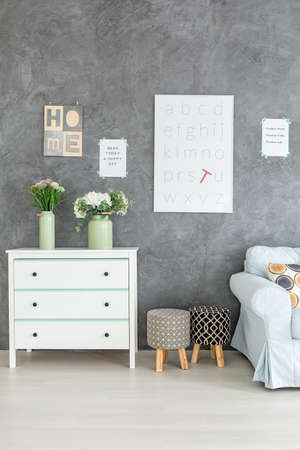 Grey room with white poster on the wall
